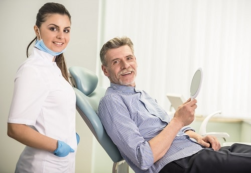 gentleman in dental chair with hygienist